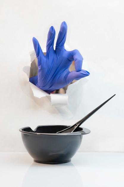Mano in guanti da parrucchiere blu attraverso un buco mostra gesto tutto bene e ciotola nera con un pennello Foto Premium