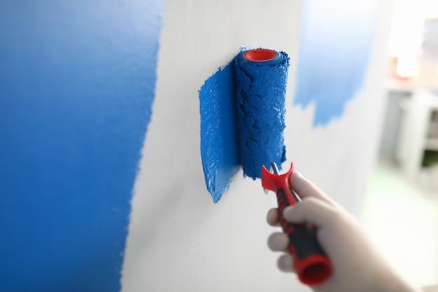 Mano in guanto bianco protettivo che dipinge un muro Foto Premium