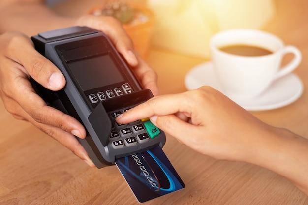 Mano inserendo il codice pin della carta di credito per la password di sicurezza nella macchina di scorrimento della carta di credito Foto Premium