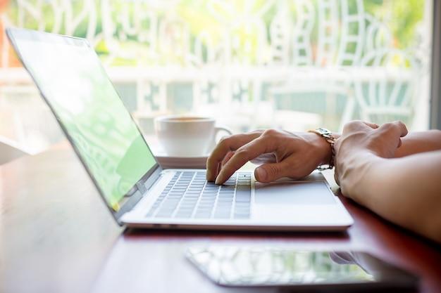 Mano maschio che scrive sul computer portatile in caffè Foto Gratuite