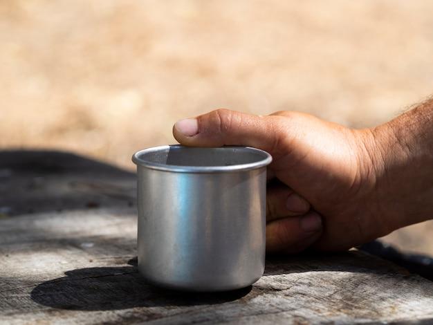 Mano maschio che tiene la tazza d'annata del metallo il giorno soleggiato Foto Gratuite