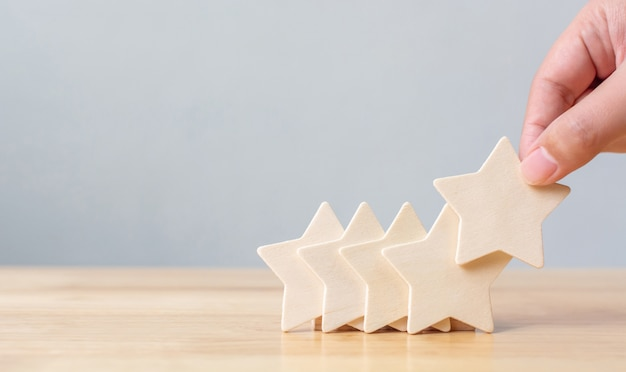 Mano mettendo a forma di stella a cinque in legno sul tavolo. i migliori servizi aziendali eccellenti valutano il concetto di esperienza del cliente Foto Premium