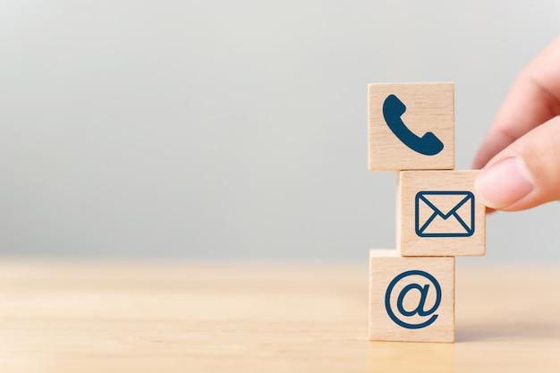 Mano mettendo il cubo di blocco di legno simbolo telefono, e-mail, indirizzo. Foto Premium