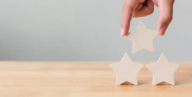 Mano mettendo in legno a forma di stella a cinque sul tavolo Foto Premium
