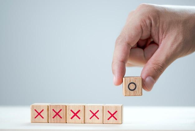 Mano mettere lo schermo di stampa simbolo o sul cubo di legno e x cubi di legno Foto Premium