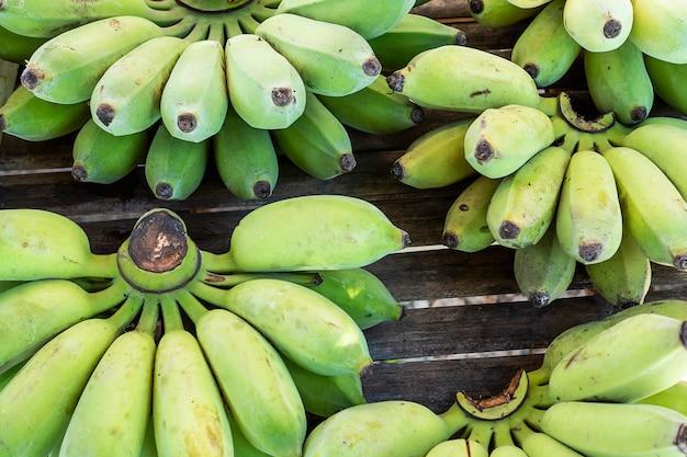 Mano organica verde fresca della banana pronta per vendere nel mercato locale della tailandia Foto Gratuite