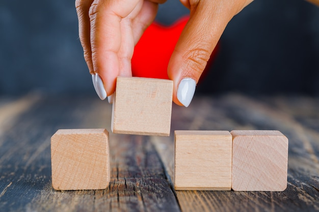 Mano prendendo cubo di legno Foto Gratuite
