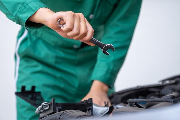 Mano professionale del meccanico che fornisce il servizio di riparazione e manutenzione dell'automobile Foto Premium