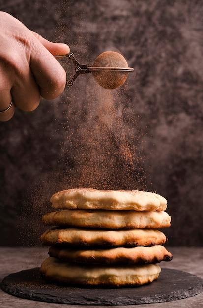 Mano setacciare il cacao in polvere sopra i pancake impilati Foto Gratuite