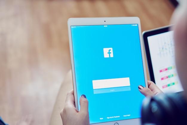 Mano sta premendo lo schermo di facebook su apple ipad pro, i social media stanno usando per informat Foto Premium