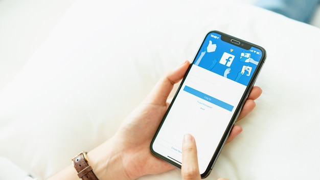 Mano sta premendo lo schermo di facebook su apple iphone x, i social media stanno usando per informa Foto Premium