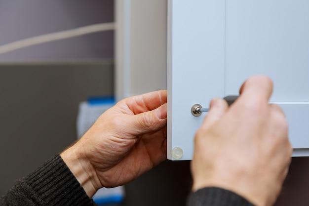 Mano sul portello di installazione della maniglia in armadio della cucina con un cacciavite Foto Premium