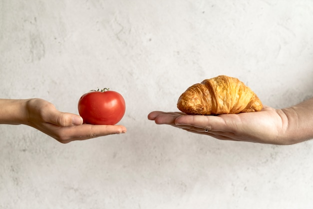 Mano umana che mostra croissant e pomodoro rosso davanti a sfondo concreto Foto Gratuite