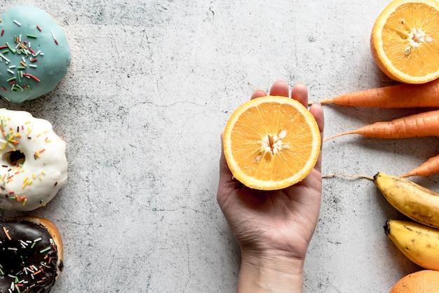 Mano umana che tiene dimezzato frutta arancione vicino a ciambelle; carote e banana Foto Gratuite