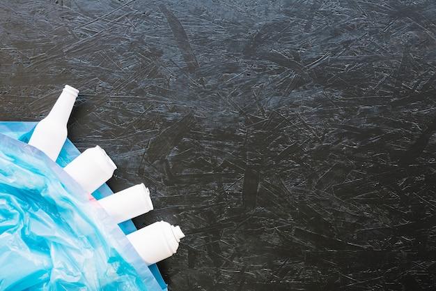 Mano umana che tiene la bomboletta spray bianca contro fondo nero Foto Gratuite