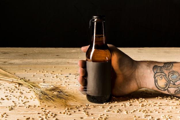 Mano umana che tiene la bottiglia alcolica con spighe di grano sulla superficie in legno Foto Gratuite