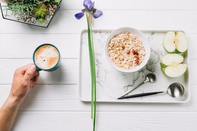 Mano umana che tiene una tazza di caffè con la prima colazione deliziosa sulla plancia di legno Foto Gratuite