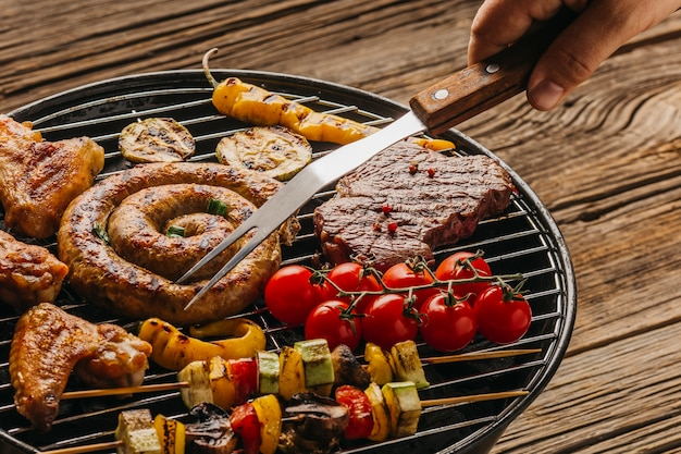 Mano umana preparando carne alla griglia e salsicce sul barbecue Foto Gratuite