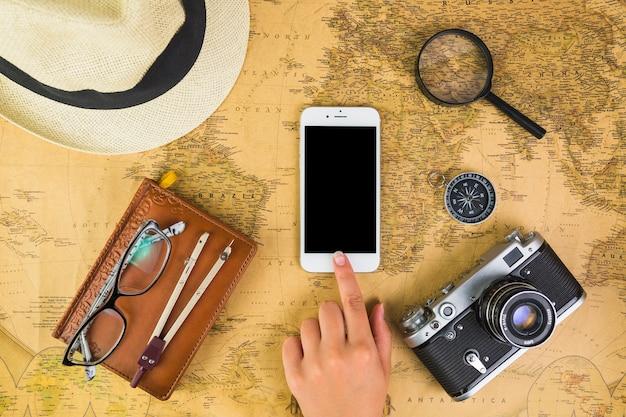 Mano umana sul cellulare con attrezzature da viaggio in giro sulla mappa Foto Gratuite