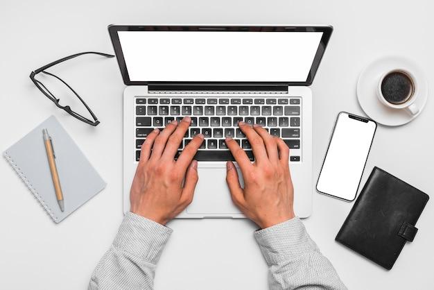 Mano umana usando il portatile con lo smartphone; bloc notes; penna; occhiali e tazza di tè sulla superficie bianca Foto Gratuite