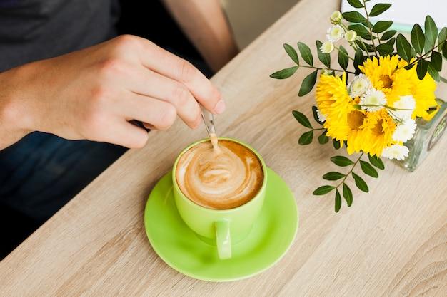 Mano umana usando un cucchiaio per mescolare il caffè nel caffè Foto Gratuite