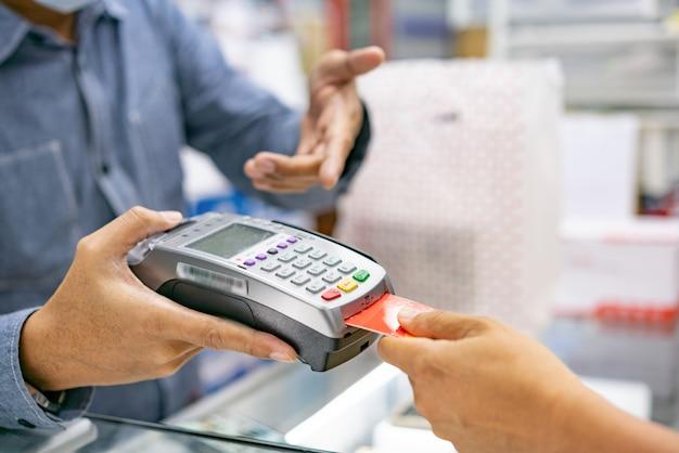 Mano usando la carta strisciante della carta di credito per pagare Foto Premium