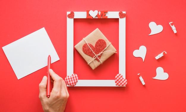 Mano vicino carta, cornice con titolo d'amore, simboli presenti e cuore Foto Gratuite