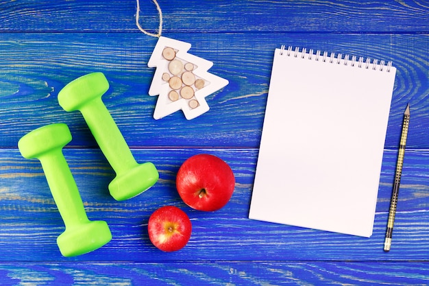 Manubri con frutta e taccuino sullo scrittorio di legno. risoluzioni salutari per il nuovo anno. Foto Premium