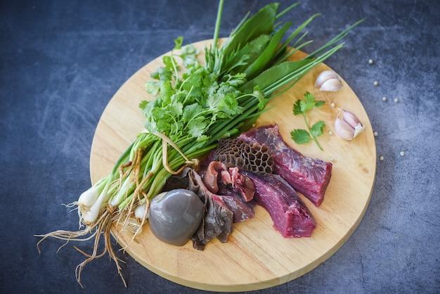 Manzo della carne cruda con l'aglio delle spezie sul tagliere di legno Foto Premium