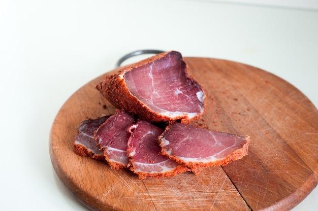 Manzo essiccato. carne di manzo affettata a scatti. carne su una tavola di legno. Foto Premium