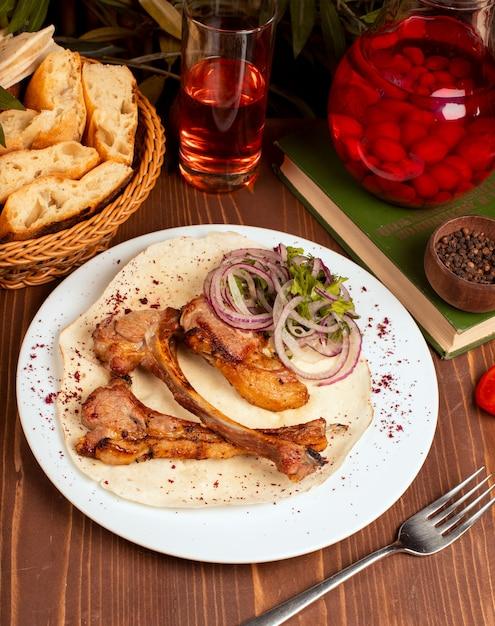 Manzo, spiedino di agnello servito con fette di cipolla, verdure ed erbe, lavash in piatto bianco. Foto Gratuite