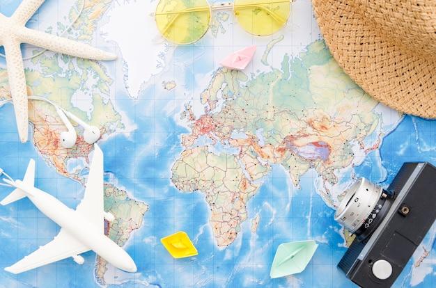 Mappa del mondo con fotocamera, aereo giocattolo e stelle marine Foto Gratuite