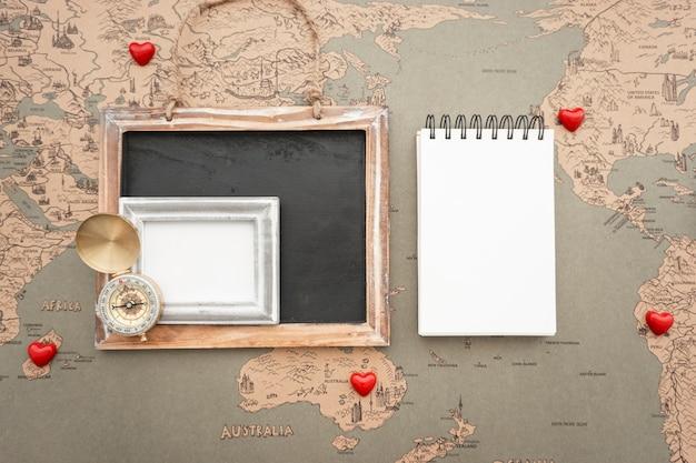Mappa del mondo di fondo con il taccuino in bianco e articoli da viaggio Foto Gratuite