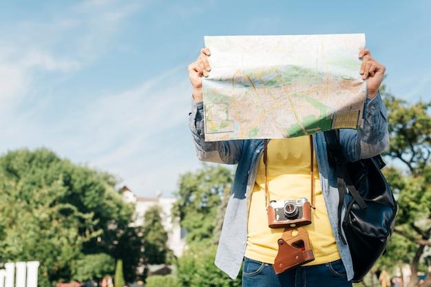 Mappa della tenuta dell'uomo del viaggiatore davanti al suo fronte con lo zaino e la macchina fotografica di trasporto Foto Gratuite