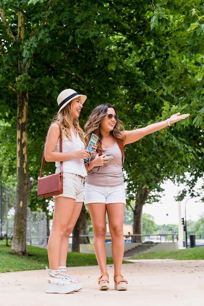 Mappa della tenuta della giovane donna a disposizione che esamina il suo amico sorridente che mostra qualcosa nel parco Foto Gratuite