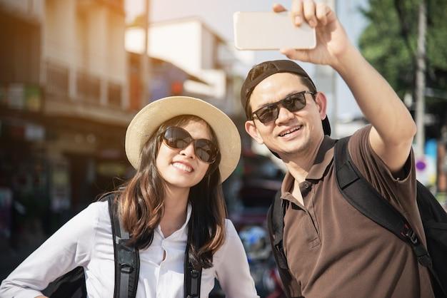 Mappa turistica della città della tenuta della coppia asiatica dello zaino che attraversa la strada - concetto di stile di vita di vacanza della gente di viaggio Foto Gratuite