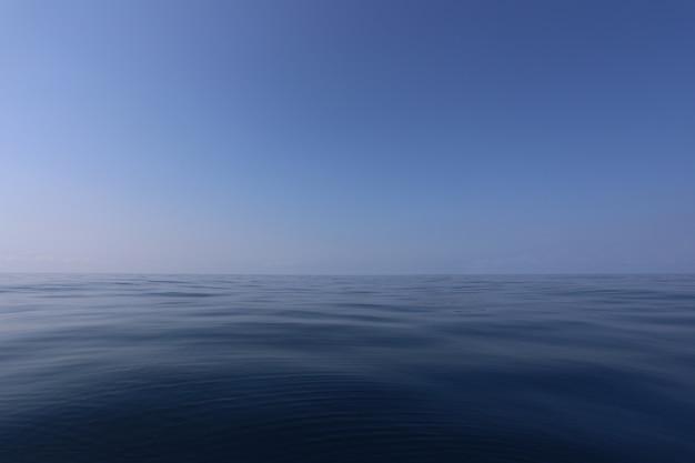 Mare liscio e cielo blu di giorno con aria limpida. Foto Premium