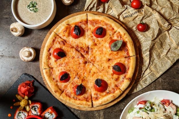 Margarita della pizza sulla vista superiore del basilico del pomodoro del formaggio del bordo di legno Foto Gratuite