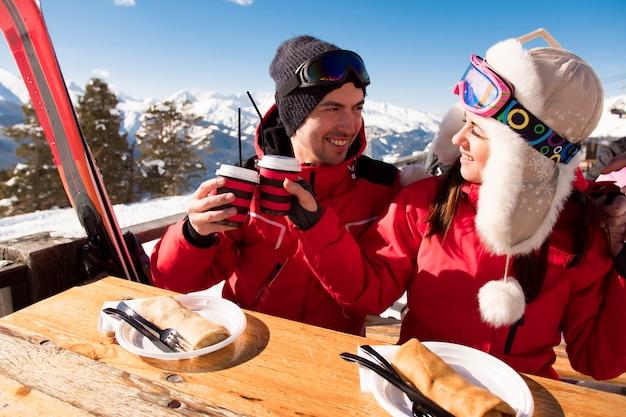 Marito e moglie si rilassano dopo lo sci divertendosi nel comprensorio sciistico Foto Premium