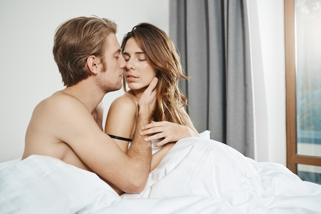 Marito seduto a letto con la moglie, tenendosi la mano sul viso e baciandosi mentre gli occhi chiusi e la mano gli toccavano delicatamente il braccio inizio di sensuali preliminari mattutini di nuovi matrimoni. Foto Gratuite