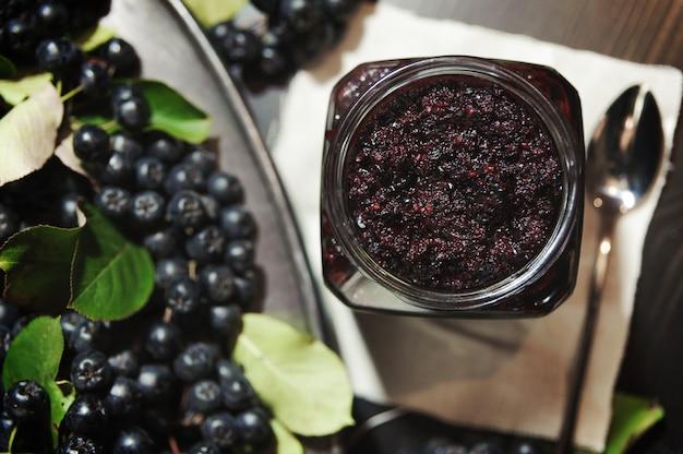 Marmellata di chokeberries neri e le sue bacche sul tavolo scuro. Foto Premium