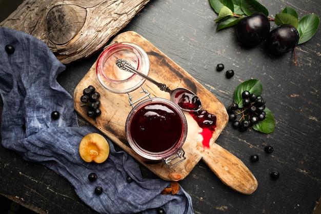 Marmellata di prugne appena fatta in un barattolo e frutti su una tavola con drappi. Foto Premium