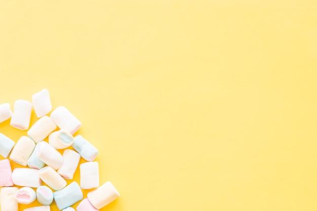 Marshmallow all'angolo dello sfondo giallo Foto Gratuite