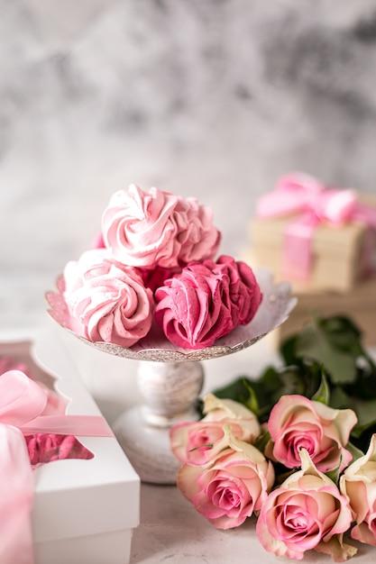 Marshmallow fatti in casa da bacche su un supporto e un mazzo di fiori Foto Premium