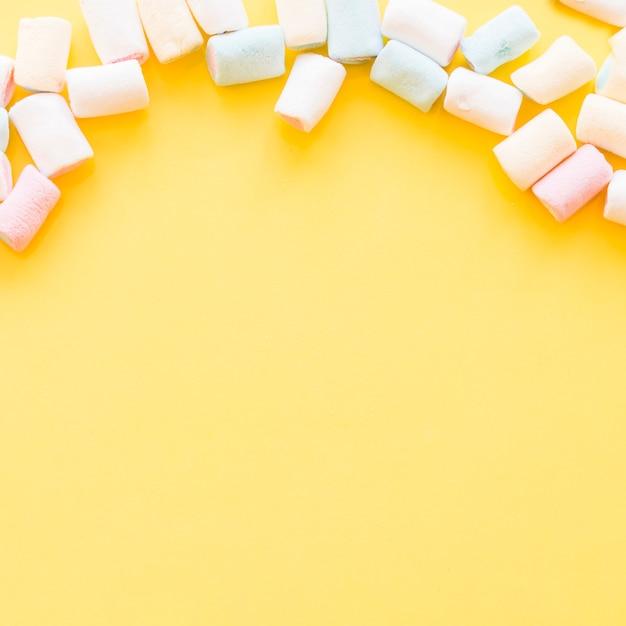 Marshmallows morbidi oltre il bordo di sfondo giallo Foto Gratuite