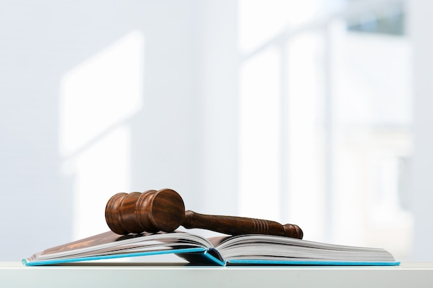 Martelletto in legno e libri sul tavolo di legno Foto Premium
