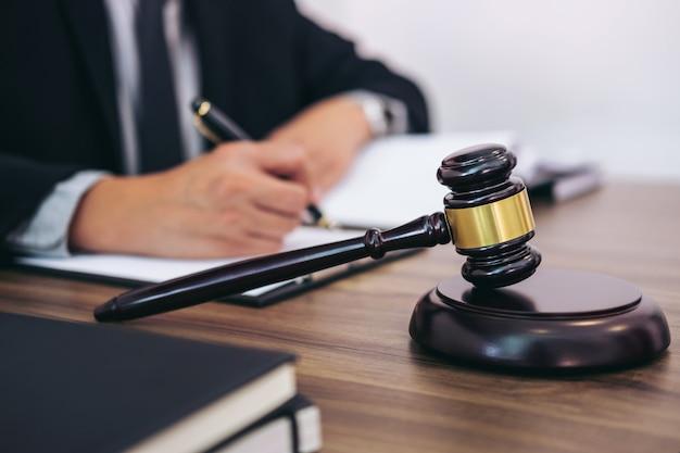 Martelletto sul tavolo di legno e avvocato o giudice che lavorano con accordo Foto Premium