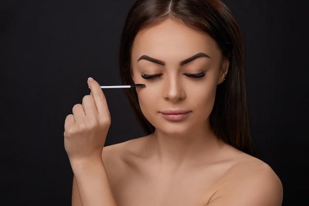 Mascara, trucco di bellezza, pelle morbida fresca e ciglia lunghe e nere che applicano mascara con pennello cosmetico, extension per ciglia, ciglia finte, Foto Premium