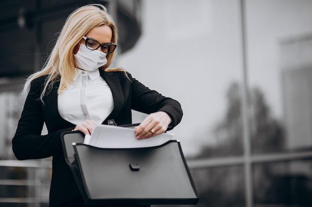 Maschera d'uso della donna di affari fuori del centro di affari Foto Gratuite