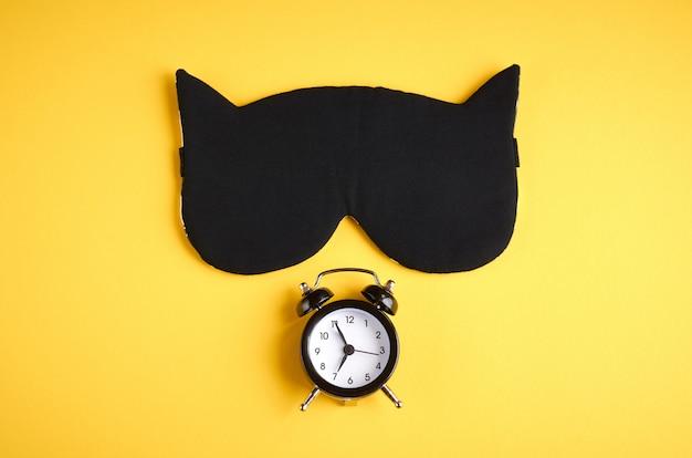 Maschera da sonno nera con orologio su composizione gialla, maschera da gatto con orecchie Foto Premium